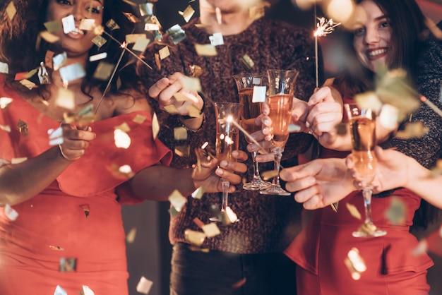 Buon umore e buon tempo. amici multirazziali festeggiano il nuovo anno e tengono in braccio luci e bicchieri di bengala