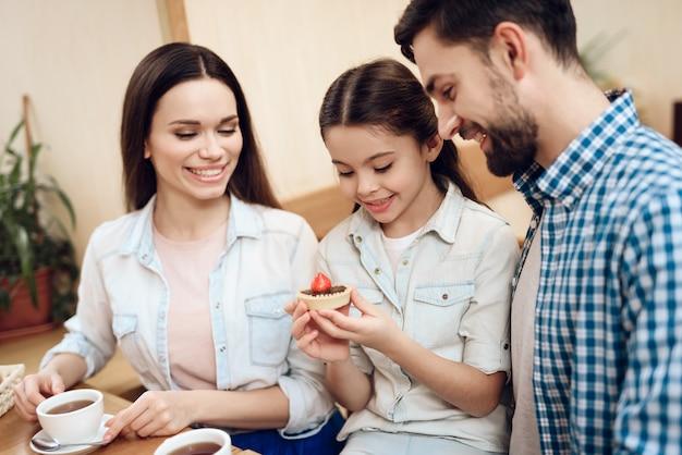 Buona famiglia felice che mangia torte in mensa.
