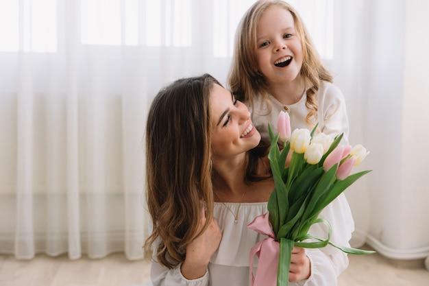 Buona festa della mamma. la figlia del bambino si congratula con le mamme e le dà i tulipani dei fiori.