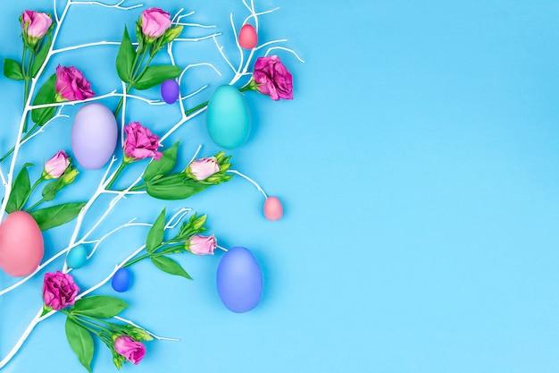 Buona pasqua. albero blu del ramo con i fiori della molla variopinta e le uova di pasqua variopinte su fondo blu