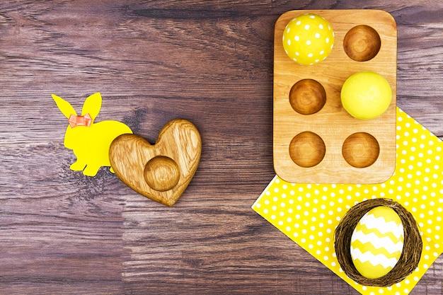 Buona pasqua. basamento di legno delle uova con le uova gialle, il centrino giallo e la siluetta gialla di coniglio
