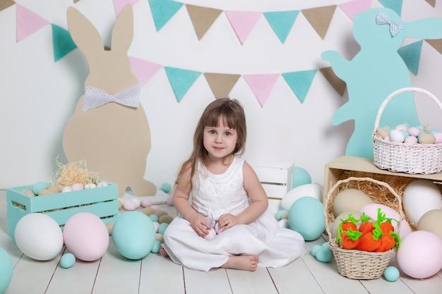 Buona pasqua!! bella bambina in un abito bianco con le uova di pasqua e un cesto su uno scenario luminoso di pasqua. coniglietto e cestino. grandi uova di pasqua, posizione colorata. festa della mamma. raccolta, agricoltore