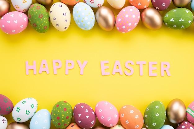 Buona pasqua! chiuda sulle uova di pasqua variopinte su fondo di carta giallo