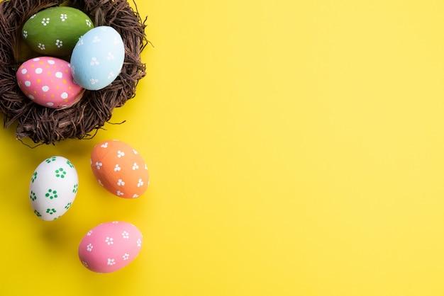 Buona pasqua! colorato di uova di pasqua nel nido con fiore e piuma