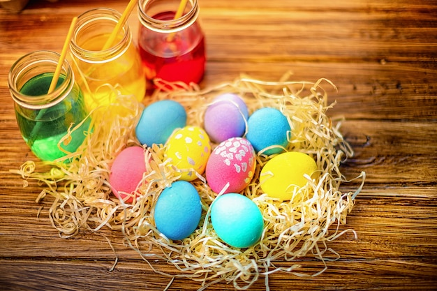 Buona pasqua con uova colorate in paglia. decorazioni da tavola per le vacanze. vista dall'alto.