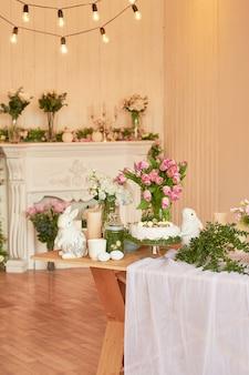 Buona pasqua! decorazioni natalizie. bella festosa tavola di pasqua con coniglietto, fiori e uova. tema di colore di primavera, copia spazio. modello di biglietto di auguri di pasqua. cucina interier.