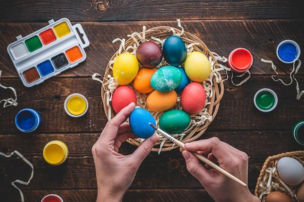 Buona pasqua. dipingere e preparare uova colorate per le vacanze di pasqua. vista dall'alto. uova colorate in un cestino su una tabella di legno, disposizione piana