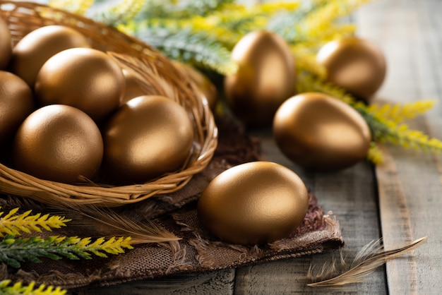 Buona pasqua! dorato delle uova di pasqua nel nido e piuma su fondo di legno