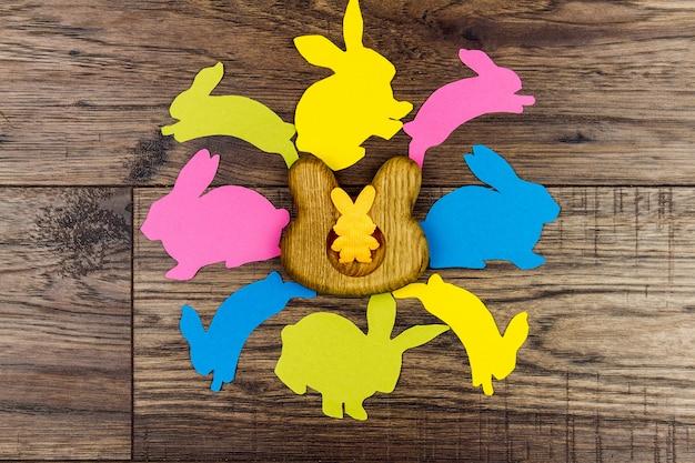 Buona pasqua. le uova di legno stanno nella forma di coniglio nel centro sul centrino giallo circondato dalle siluette dei conigli variopinti sulla tavola di legno