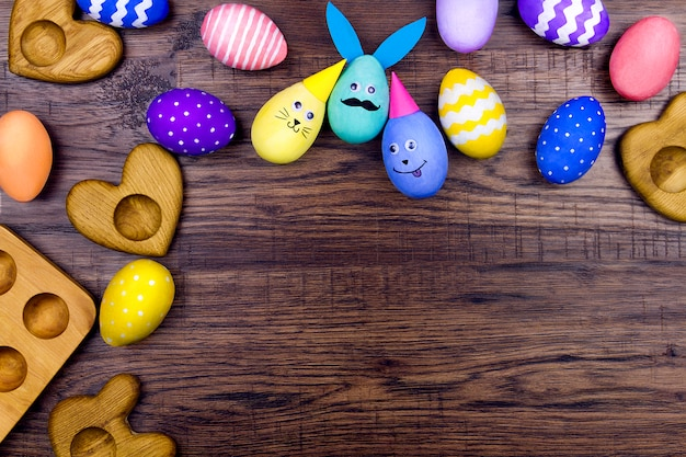 Buona pasqua. piatti di legno per le uova a forma di cuore e le uova di pasqua divertenti variopinte su fondo di legno