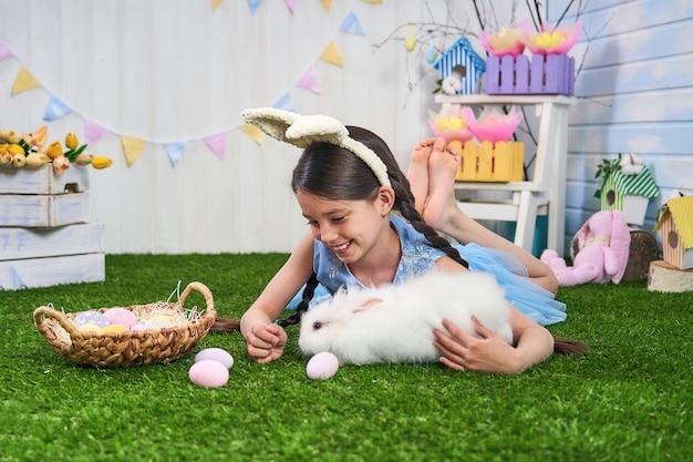 Buona pasqua! ragazza sveglia che si trova sull'erba con le uova di pasqua e un coniglio.