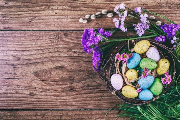 Buona pasqua. sfondo di pasqua le uova variopinte luminose in nido con la molla fiorisce sopra fondo scuro di legno