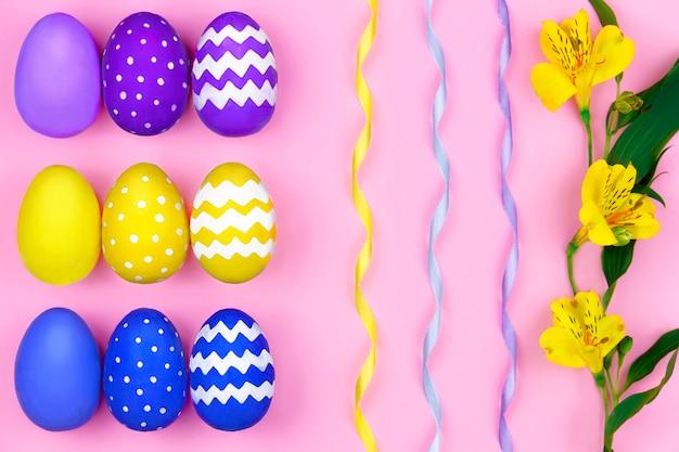 Buona pasqua. uova di pasqua viola, gialle e blu, nastri colorati e fiori gialli