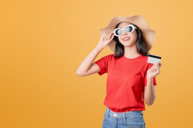 Buona pelle della bella donna asiatica, occhiali da sole d'uso che posano tenendo il pagamento con carta di credito sull'arancia.