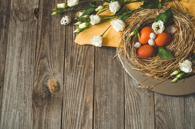 Buona tavola di pasqua. uova di pasqua in un nido su una piastra di metallo su una tavola di legno. buona pasqua