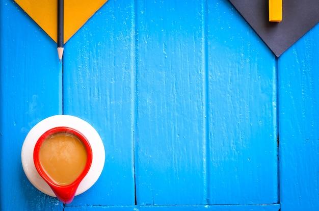 Buongiorno parola, cancelleria con una tazza di caffè su sfondo blu