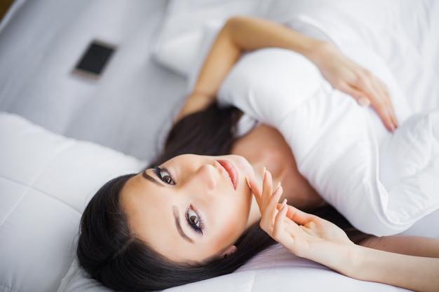 Buongiorno, ritratto di una bella giovane donna bruna sorridente che si distende nel letto bianco