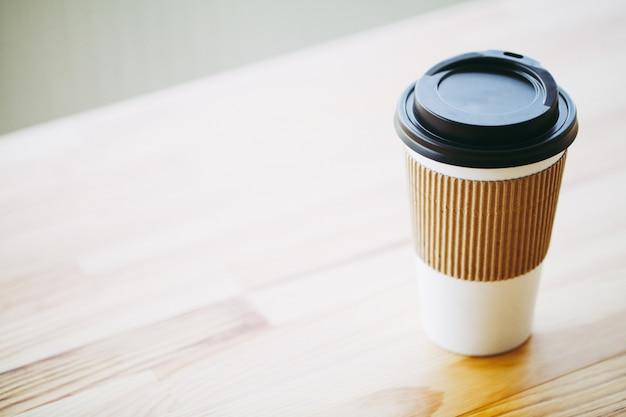 Buongiorno, tempo del caffè, caffè per andare e fagioli su un fondo di legno