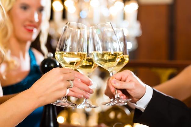 Buoni amici che bevono vino e bicchieri tintinnanti