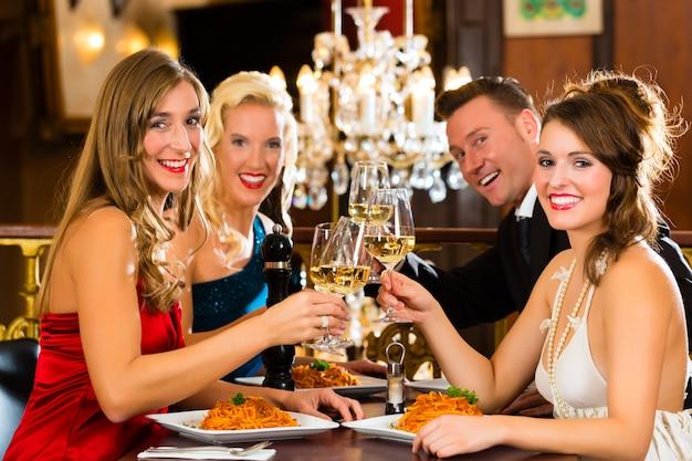 Buoni amici per cena o pranzo in un buon ristorante, bicchieri tintinnanti