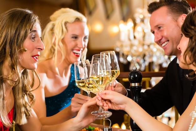 Buoni amici per cena o pranzo in un raffinato ristorante, bicchieri tintinnanti