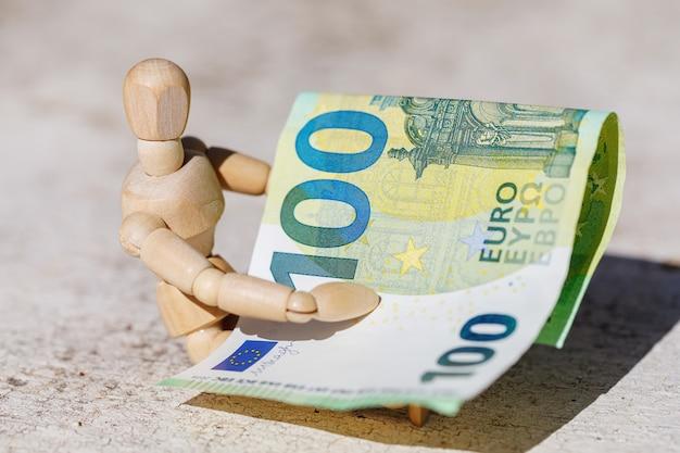 Burattino fittizio di legno che tiene centesima euro banconota. concetto di affari
