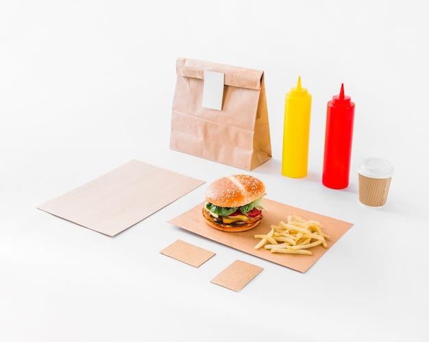 Burger; patatine fritte; pacco e bottiglia di salsa su sfondo bianco