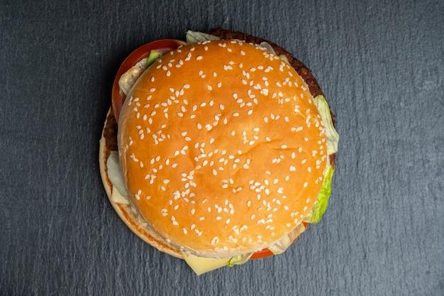Burger su un'ardesia, stoviglie in pietra nera. vista dall'alto.