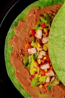 Burito messicano con salsa e pepe. burito con contorno in ristorante servito a pezzi.