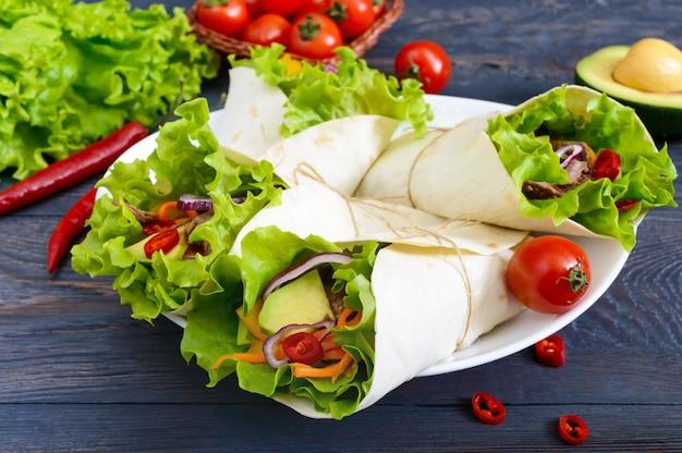 Burrito con carne tritata, avocado, verdure, peperoncino su un piatto su uno sfondo di legno scuro. tortilla ripiena. antipasto messicano tradizionale.