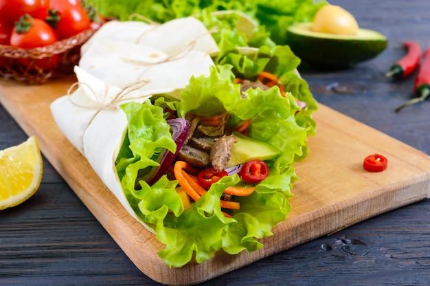 Burrito con carne tritata, avocado, verdure, peperoncino su un tagliere su uno sfondo di legno scuro. tortilla ripiena. antipasto messicano tradizionale.