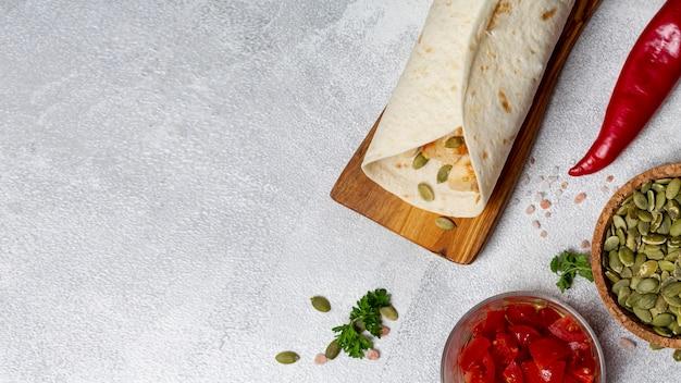Burrito vicino a peperoni, semi di cardamomo e pomodori a fette