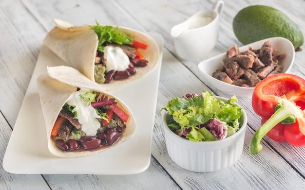 Burritos con ingredienti sul tavolo di legno