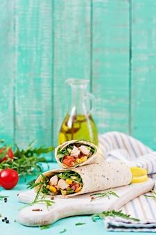 Burritos impacchi con pollo e verdure su sfondo chiaro.