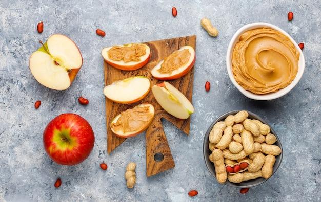Burro di arachidi casalingo con le arachidi sulla tavola di calcestruzzo grigia, vista superiore