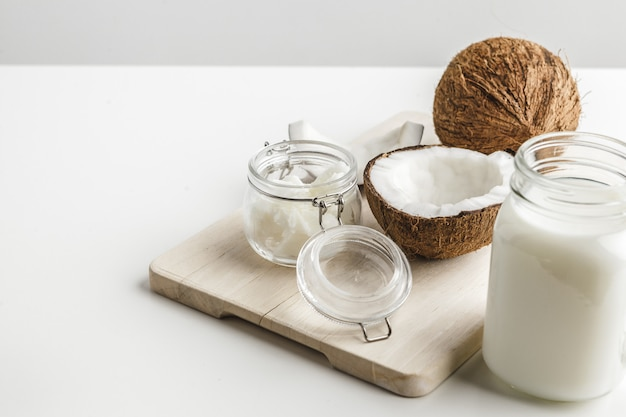 Burro di cocco sano organico e pezzi freschi della noce di cocco sul bordo di legno