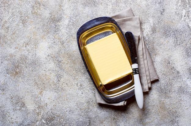 Burro e coltello freschi nel piatto di burro
