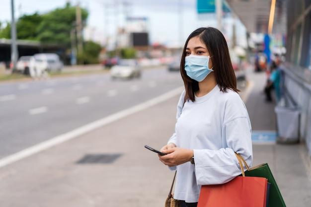 Bus aspettante d'uso dello smartphone e del sacchetto della spesa della tenuta della maschera di protezione della donna alla fermata dell'autobus in via della città