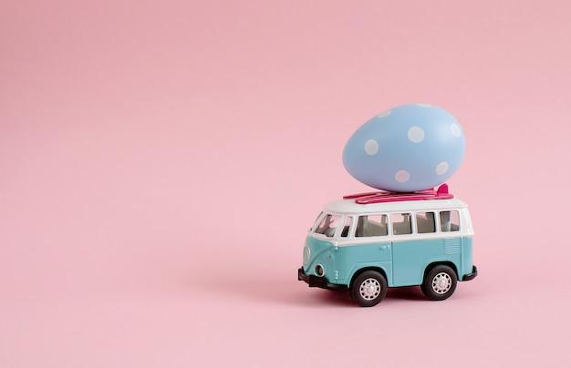 Bus del hippie con le uova variopinte di pasqua sull'insegna miniatura dell'automobile del tetto piccola