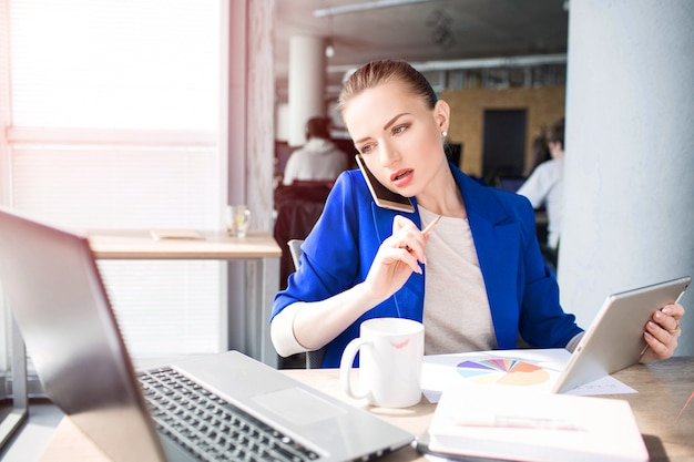 Bus giovane donna è seduta al tavolo e parlando al telefono