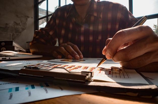 Business designer è in possesso di una penna per scrivere un grafico di reddito di investimento di successo.