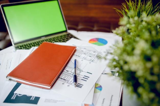 Business desk con business notebook, scrivania, penna, carta, grafico della tabella