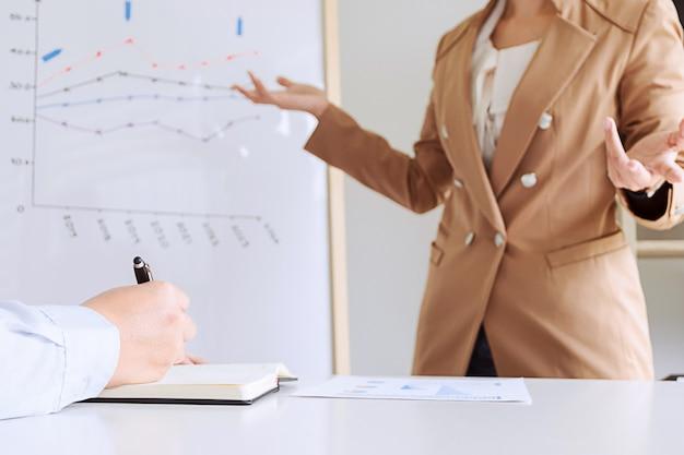 Business executives brainstorming discutendo performance vendita su bordo bianco, mentre la presentazione in sala ufficio moderna