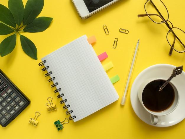 Business piatta giaceva con copia spazio, calcolatrice, matita, blocco note, bicchieri da caffè su sfondo giallo colorato