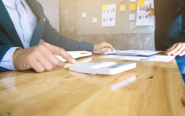 Business team che utilizza un documento di dati di analisi calcolatrice e utilizza calcolatrice