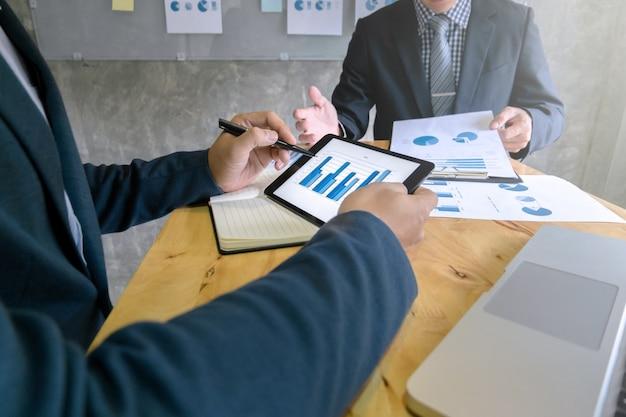 Business team disscussing su tavoletta digitale in una riunione