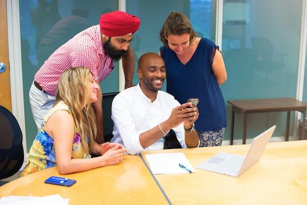 Business team formato da diverse etnie in ufficio che guardano il cellulare