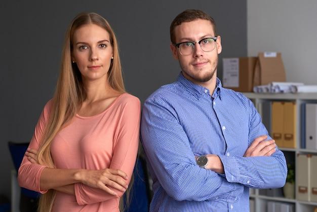 Business team in piedi spalla a spalla braccia conserte