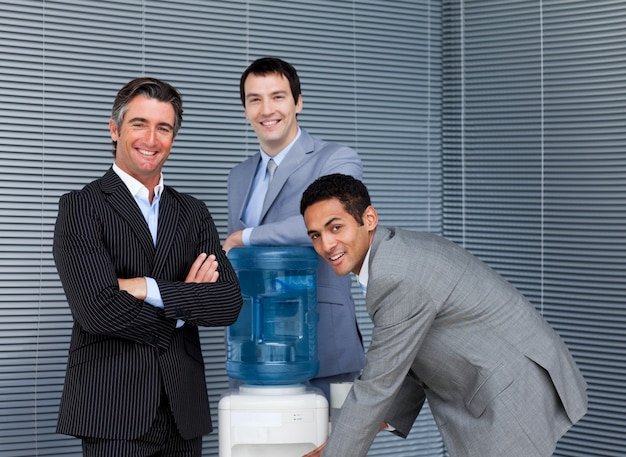 Business team multietnico al refrigeratore d'acqua