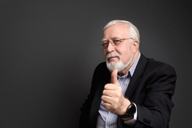 Business, uomo dai capelli bianchi in bicchieri su uno sfondo grigio sorride e mostra approvazione